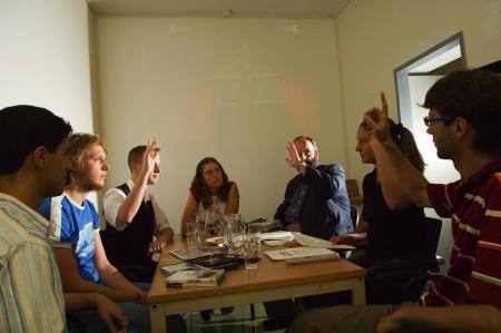 Mehrere Personen um einen Tisch bei einer Abstimmung mit Handzeichen