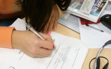 Eine Hand mit Stift füllt einen Bewertungsbogen aus