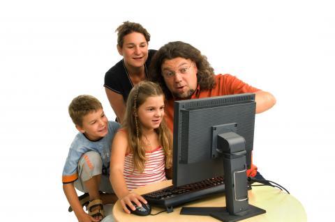 Eltern und zwei Kinder vor einem Bildschirm