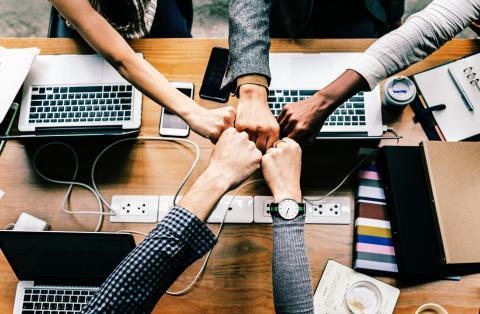 5 Personen strecken über einem Arbeitstisch, vollgestellt Laptops, ihre Fäuste zusammen, sie sind ein Team